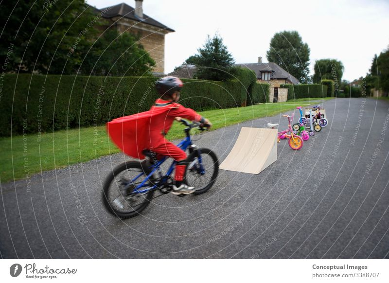Young boy riding bicycle towards ramp action adrenaline adventure bicycling bike biker biking blurred blurred motion bmx child childhood concept danger