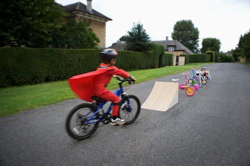 Young boy riding bicycle towards ramp action adrenaline adventure bicycling bike biker biking blurred blurred motion bmx child childhood concept danger