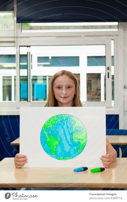 Primary school caucasian girl holding placard with an image of the earth drawing planet schoolchild environment female education ecology future conservation