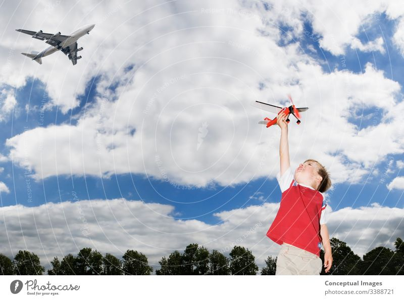 Young boy playing with a toy planeYoung caucasian boy playing with a toy plane as a passenger plane flies overhead themes of future imagination inspiration