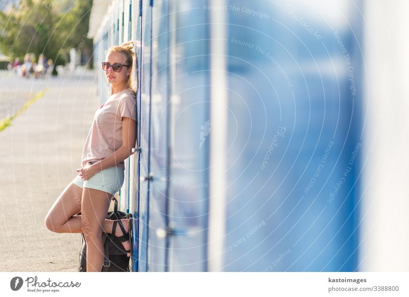 Blonde young female traveler wearing summer style clothing, leaning against retro blue beach dressing rooms at summer time vacation in Sistiana, Italy woman