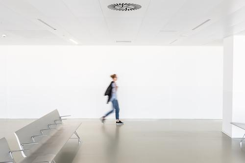 Motion blur of woman walking at contemporary white empty hallway interior architecture motion seats terminal modern room caucasian female blurred health light