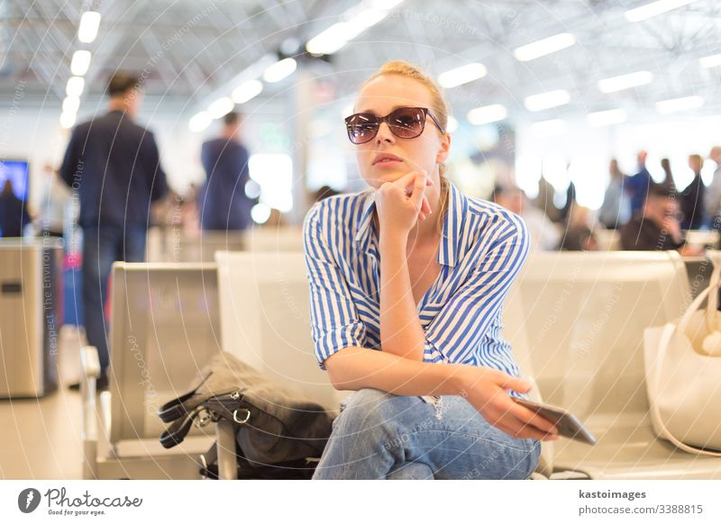 Woman using her cell phone while waiting to board a plane at departure gates at international airport. woman travel sitting ticket beautiful passenger female