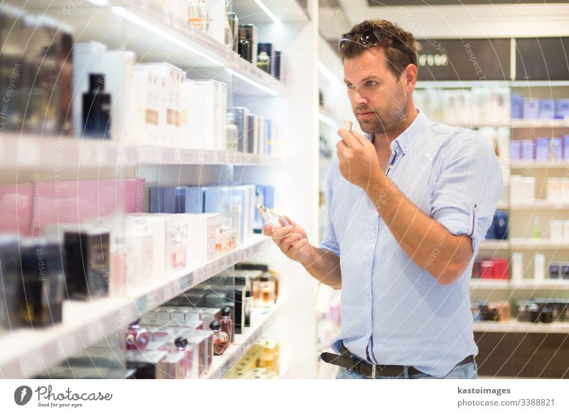 Elegant man choosing perfume in retail store. customer shop shopping beauty guy cosmetic person attractive male drugstore holding buy consumerism clients