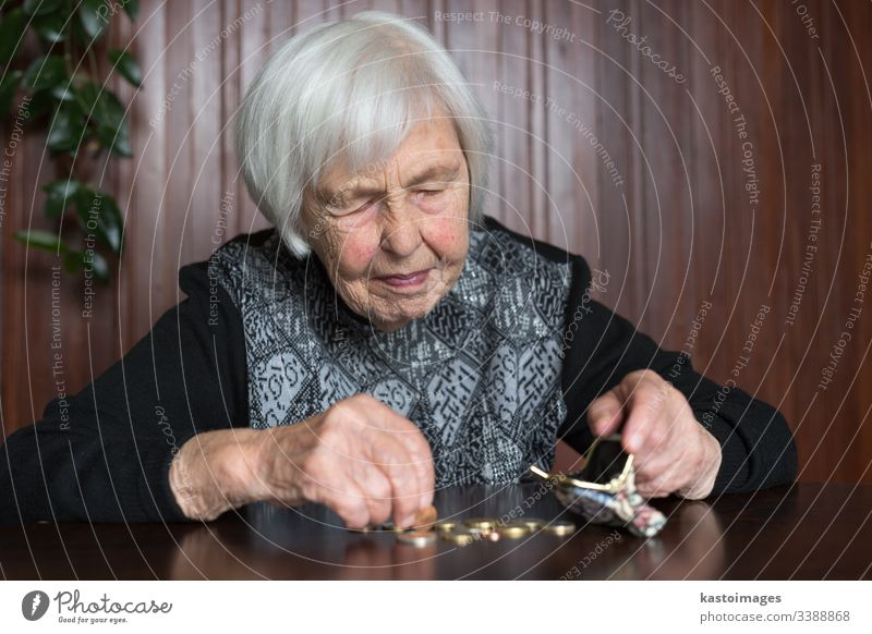 Elderly woman sitting at the table counting money in her wallet. senior pensioner elderly poverty retirement old empty coins background miserable broke lonely