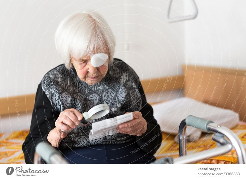 Visually impaired elderly 95 years old woman sitting at the bad trying to read with magnifying glass. senior vision eyesight visually impaired pensioner care
