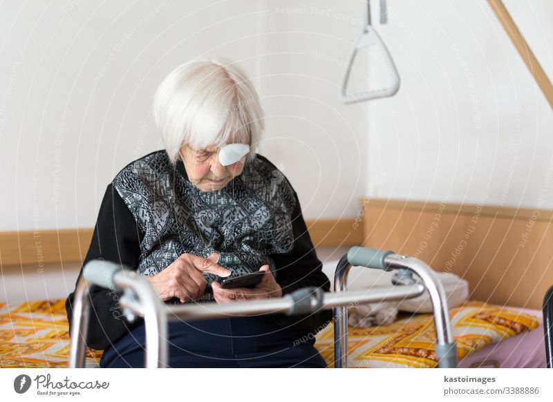 Lonley elderly 95 years old woman sitting at the bad using modern mobile phone. senior pensioner care disability hospital mobility home citizen clinic retiree