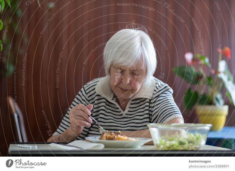 Solitary senior woman eating her lunch at retirement home. pensioner elderly wallet poverty old retired grandmother person dining dinner meal caucasian food