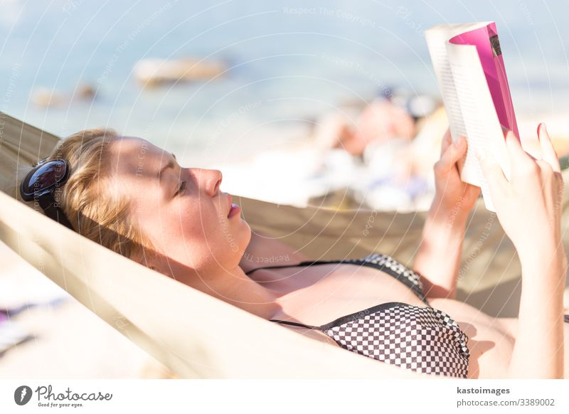 Woman reading book in hammock on the beach vacation day female woman relax young novel relaxation rest summer leisure lying human idyllic person resort relaxing