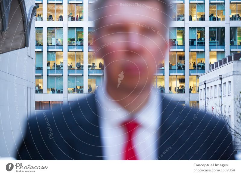 Defocussed businessman looking at the camera at dusk adult adults only business person city city life commuter corporate business day defocussed departure