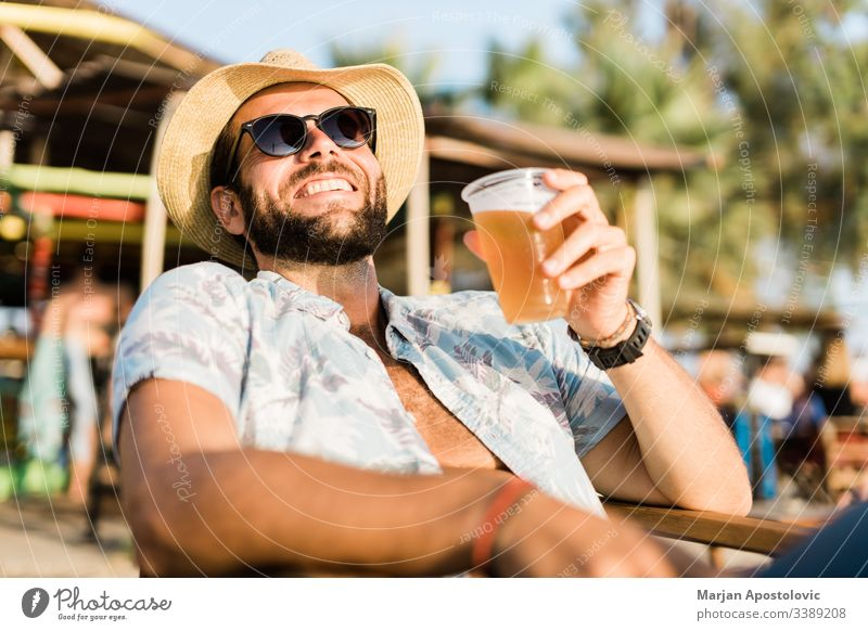 Young handsome man enjoying beer in beach bar 30s adult alcohol bearded beverage casual caucasian cheerful cheers cool destination drink fun happy hat hipster
