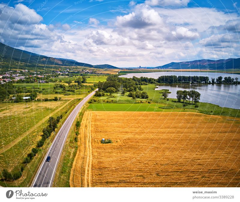 Summer landscape with fields, meadows, lake and mountains. Road on the lakeside water summer aerial Slovakia panorama alpine Tatras park hill outdoor