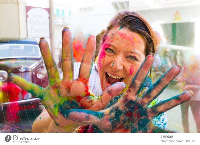 woman having fun at holi festival showing her coloured hands in the camera excited crazy enjoying festival of colours tourism concept happiness summer holy