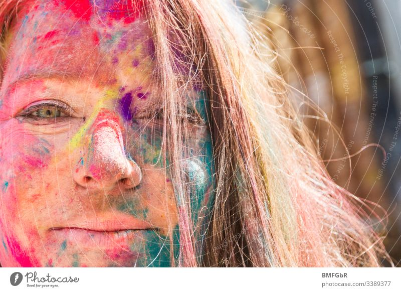 happy woman portrait with colors from holy festival in her face excited crazy enjoying festival of colours tourism concept happiness summer fun travel india