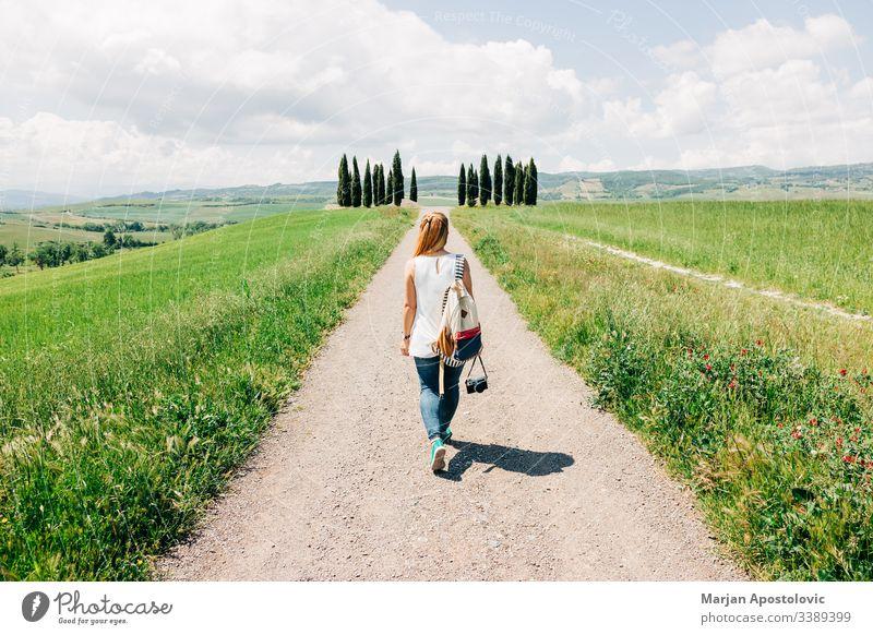 Young female traveler walking in Tuscany countryside beautiful camera casual cypress cypresses dreamland enjoying europe european explorer girl green holidays