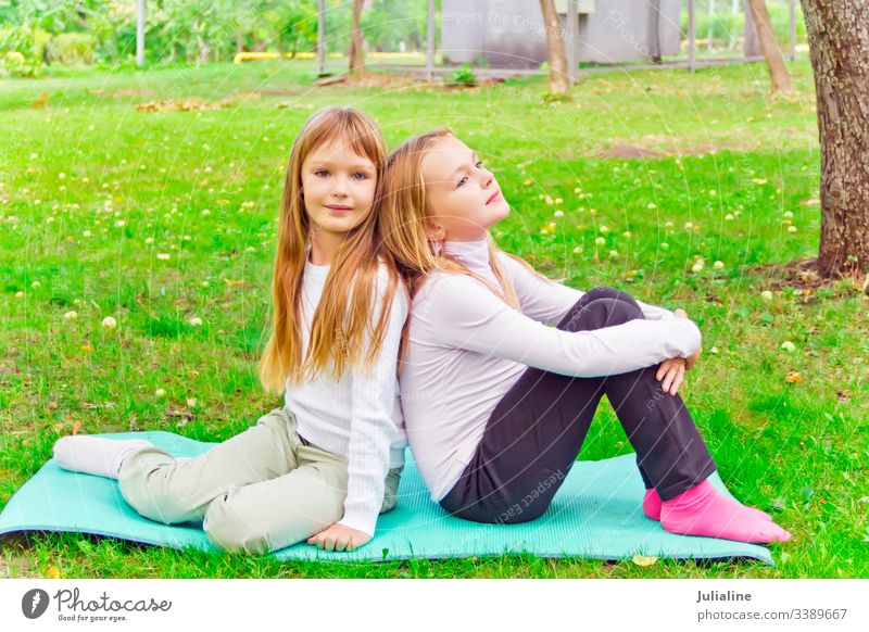 Two seven years old girls sitting on green grass sister play two female lifestyles leisure activity recreational child kid smiling preschooler schoolgirl six