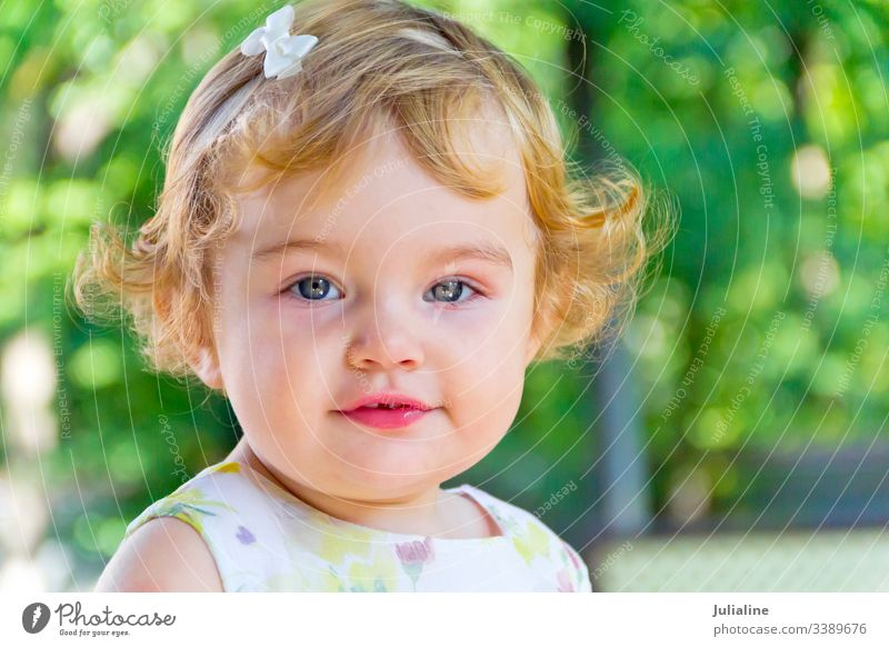 Cute infant with curly blond hair baby newborn child suckle nipple kid girl one two three first white female European Caucasian curls ringlets lady childhood