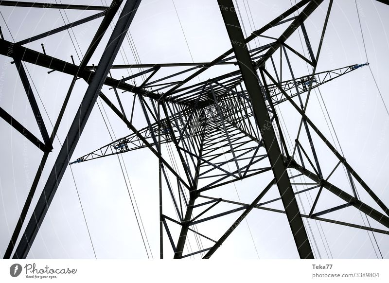 an electricity pylon from below horizontal energy cable Electricity pylon high voltage energy tranportation ampstorm sun lightning power plant power cable