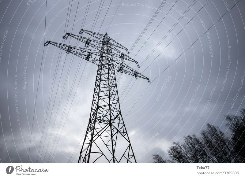 an electricity pylon in a winter sky energy cable Electricity pylon high voltage energy tranportation ampstorm sun lightning power plant power cable colors blue