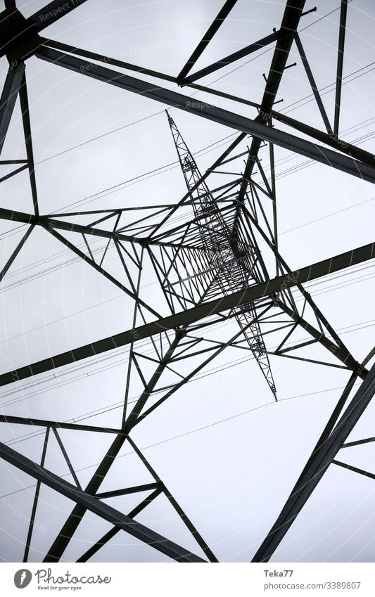 an electricity pylon from below perpendicular energy cable Electricity pylon high voltage energy tranportation ampstorm sun lightning power plant power cable