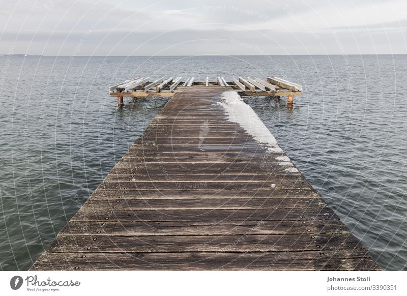 Wooden jetty with snow on the Baltic Sea shore Footbridge investor wharf wooden walkway Gangway Harbour bank Beach Ocean Lake lake view ostssee Keel boat ship
