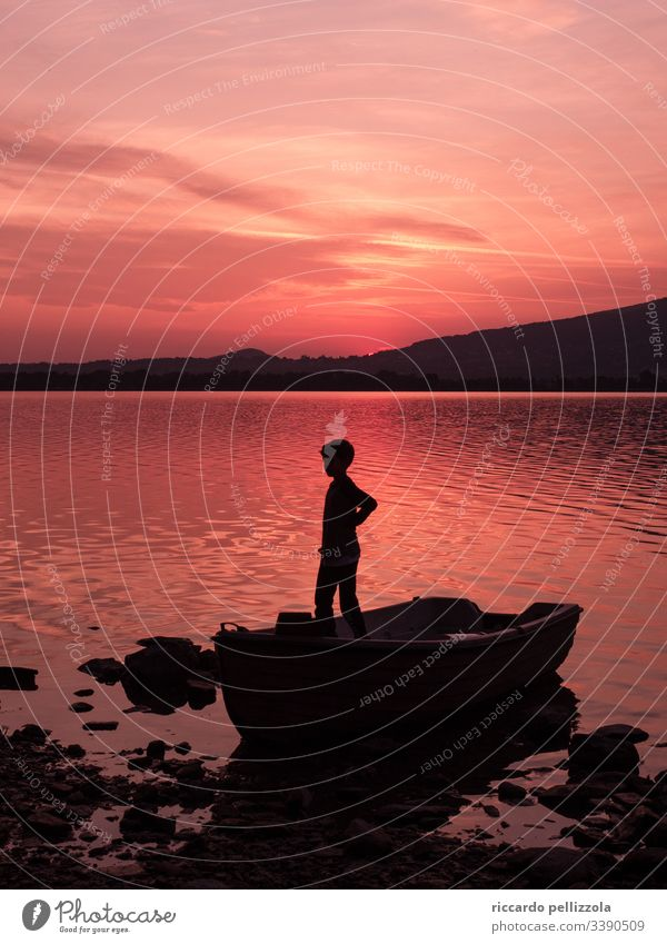 sunset on a lake with a child in a boat Sunset sunsetlake silhouette of child Child red purple Human being Silhouette Boy (child) Evening Blue Sky rocks Clouds