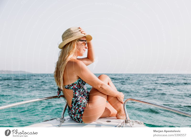 Young woman enjoying on deck of a boat on the sea young ocean water cruise leisure relaxing vacation summer holiday travel tourism sunbathing bow hat blonde