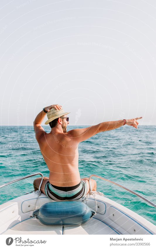 Young man on the bow of the boat enjoying the view of the sea adult adventure aegean arms blue cruise day deck free freedom fun greece happy holiday horizon