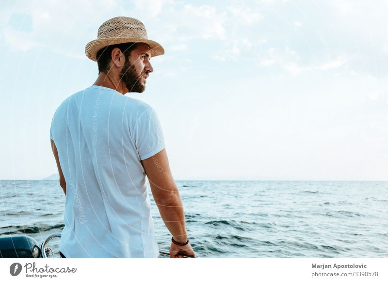 Young man enjoying a ride on a boat on the sea young handsome bearded casual adventure ocean water waves cruise speedbo nautical male summer vacation holiday