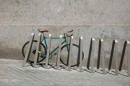 Racing bike on bicycle stand in front of grey wall Turquoise Blue Green Wheel Bicycle fixy Racing cycle city bike Tire Frame Handlebars Coat Valve Bell Pillar