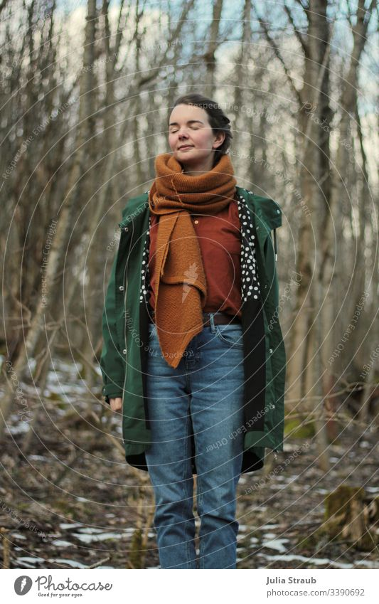 Woman standing in the forest with closed eyes Forest trees Clouds Coat Scarf shirt blouse Jeans Spotted Breathe Closed eyes Belt ochre Green Exterior shot