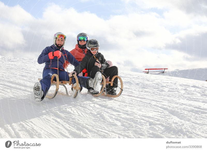 Three girls have fun sledding Girl Sports Winter sports Mountain Powder snow Downward Ski run Winter vacation Alps out Snowscape Snowcapped peak Ski-run