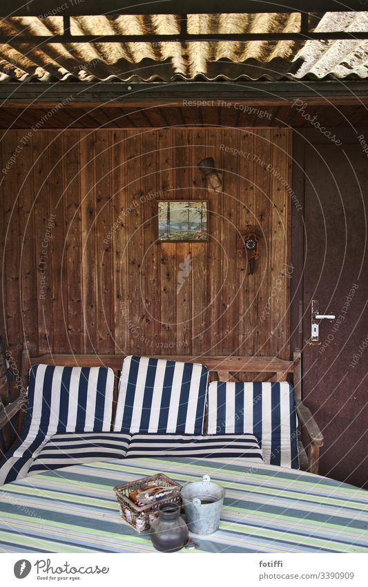 View into an abandoned allotment arbour with striped seat cushions Garden plot Cushion Striped forsake sb./sth. Deserted Interior shot Relaxation petty