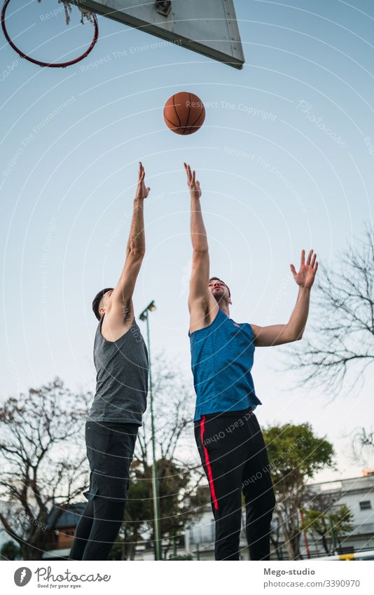 Two young friends playing basketball. game youth sport court male team together active action playground exercise men friendship jump happy athlete fitness