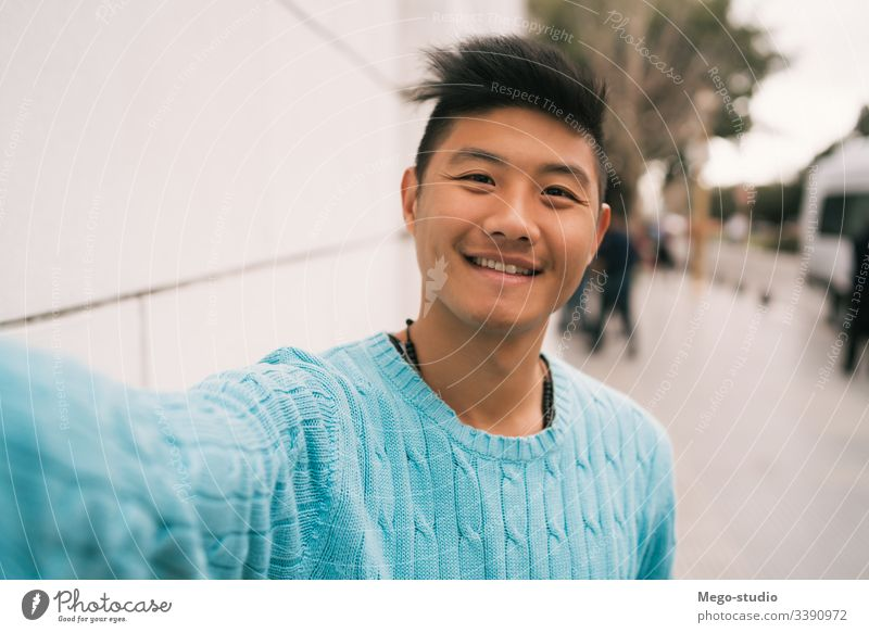 Asian man taking a selfie. confident looking guy asian background smile men face urban city life profile cheerful picture front photography holding street