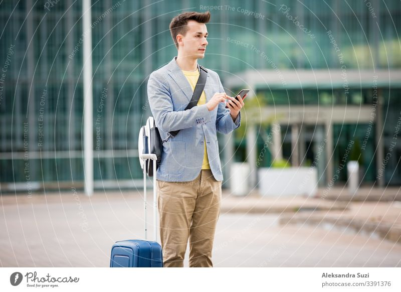 Stylish man standing at airport with smartphone and suitcase, browsing, texting, using mobile app. Business traveling. application arrival bag business