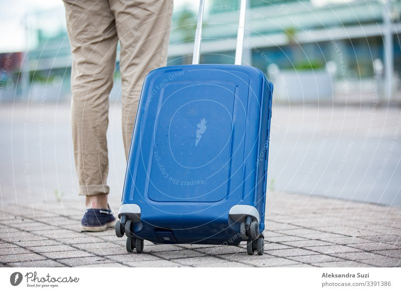 Stylish man walking to airport with blue suitcase. Businessman traveling. arrival bag baggage building business businessman carry casual city clothing confident
