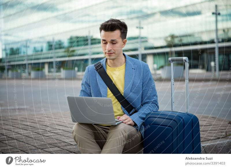 Stylish man sitting at airport with suitcase and laptop, working, typing, browsing. Businessman traveling. adult bag baggage business businessman busy caucasian