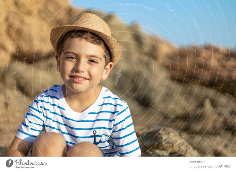 Portrait of a cute child sitting on a rocks near the sea anchor baby background beach beautiful blond blue boy bright caucasian childhood coast eyes fun