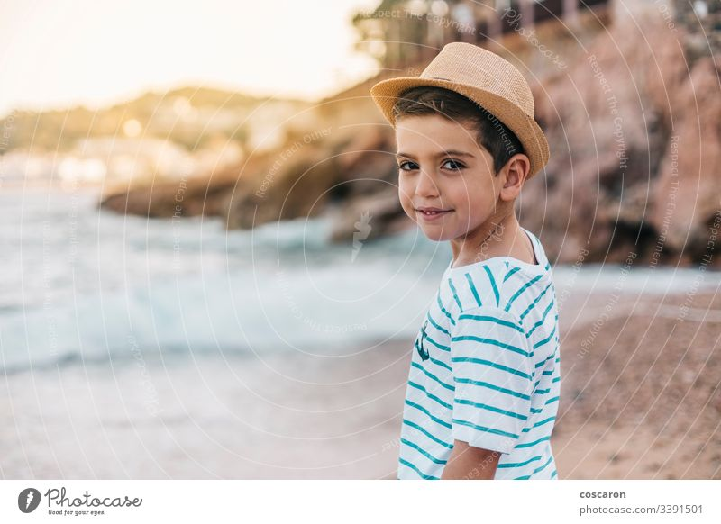 Little kid with hat looking the sea on the beach back background beautiful blue child childhood children coast contemplation cute enjoying fashion fashionable