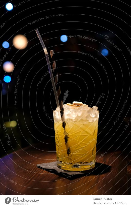 Refreshing cocktail in a bar with bokeh lights in the background Cocktail bar Cocktail glass Refreshment nightlife Night life Ice cube Straw Delicious Tasty