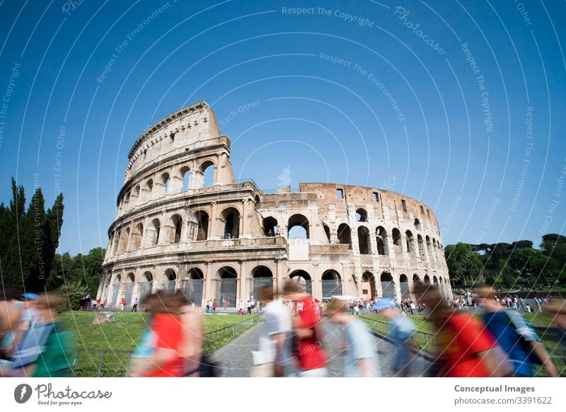 Tourists walking past the Colosseum during the day. Rome. Italy. amphitheater ancient archeology architecture arena cityscape coliseum colosseum culture
