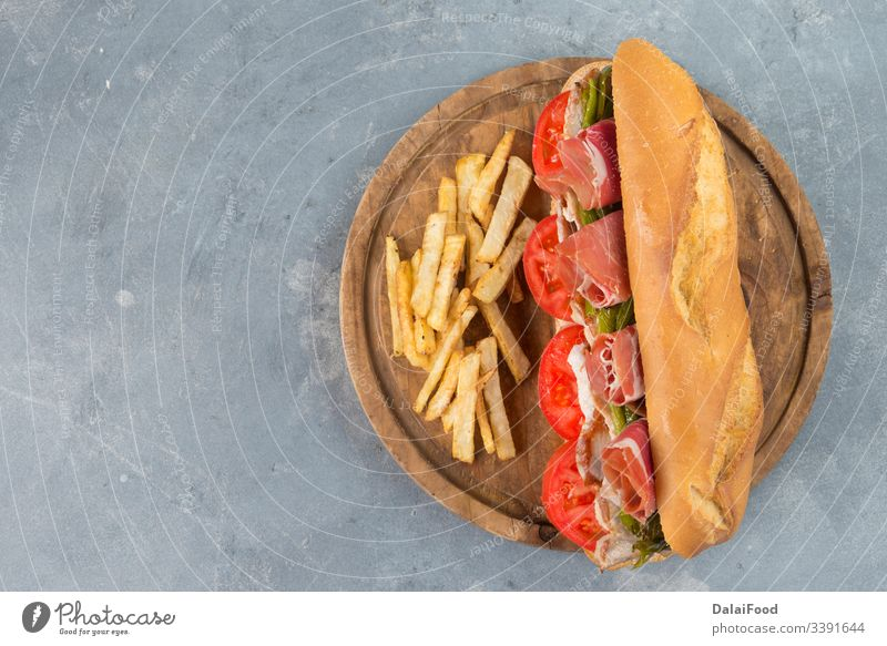 Sandwich Serranito typical in Andalusia with ham, gren pepper and grilled pork loin andalucia andalusia bacon bocadillo bread breakfast green pepper italian