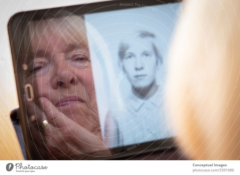 Senior caucasian woman looking at old photos of herself as a young woman on a tablet computer photography themes memories the ageing process contrasts