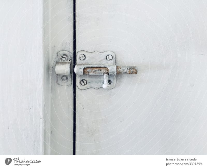 lock on the white door old dirt dirty wooden abandoned close open Minimalistic background surface screws