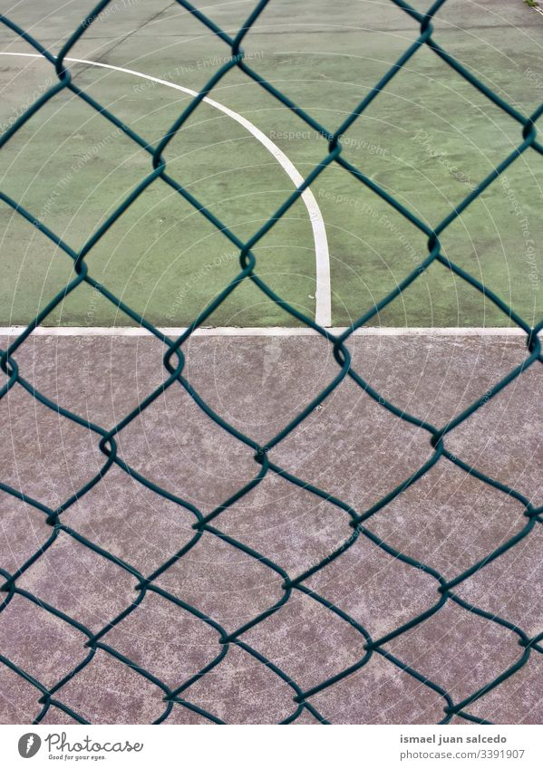metallic fence on the soccer field on the street in Bilbao city Spain court red goal net web rope sport sports equipment play playing abandoned old park