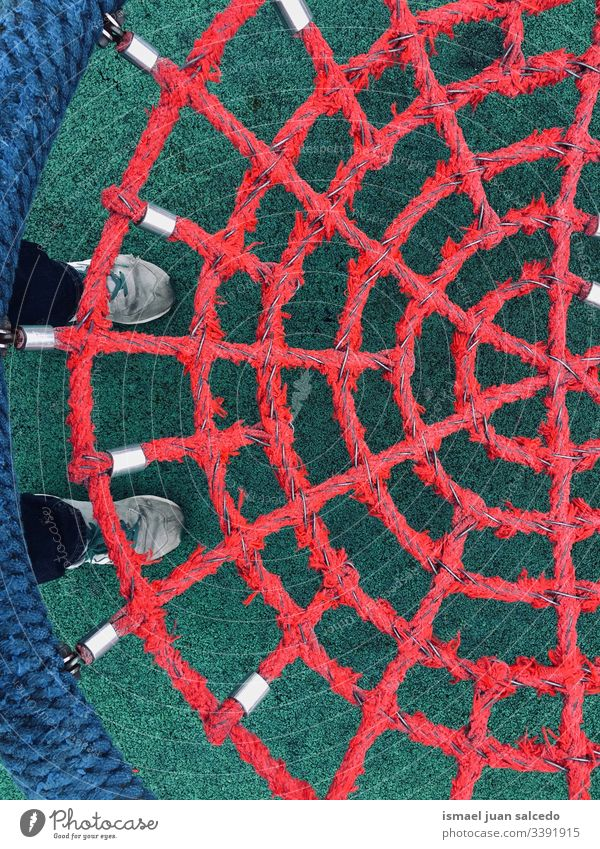 swing with red rope net playground abstract childhood playful funny sneakers feet