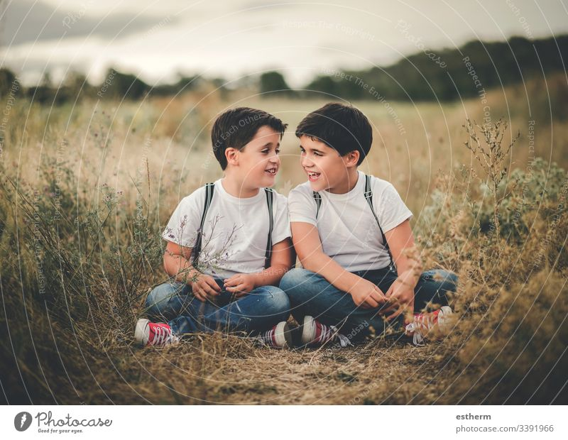 smiling brothers sitting in the field children boys twins conversation siblings family union lifestyle complicity friends smile smiles friendship fun game grass