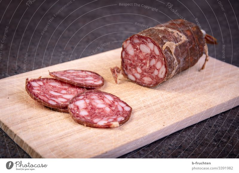 Raw sausage cut into slices on a wooden board Sausage snack time Wooden board Snack board Break Unhealthy Fat Salami Fresh Eating Deserted Food Meat Close-up