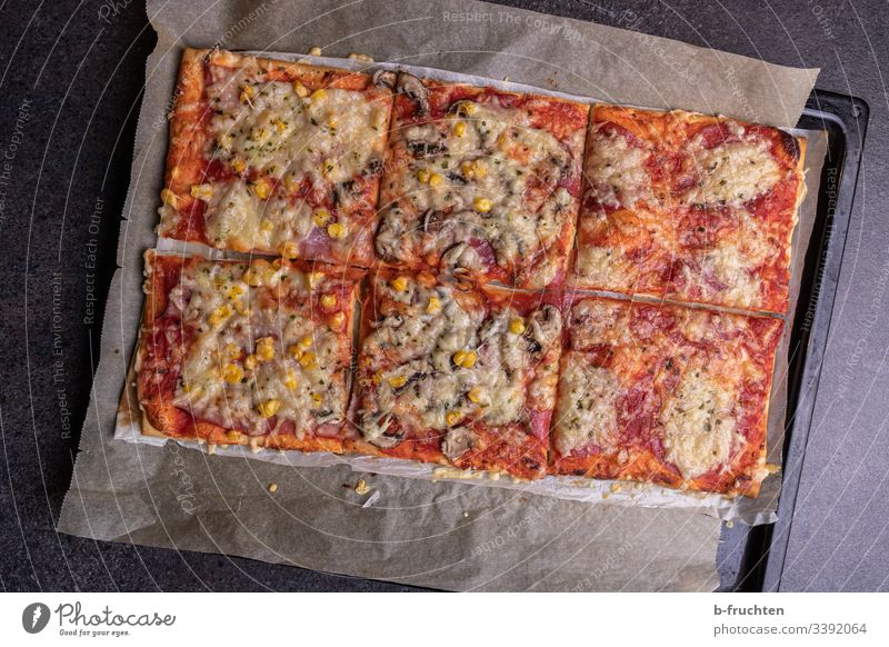 Homemade pizza on a baking tray, cut into pieces Pizza homemade Self-made baked Baking Fresh Baking tray Kitchen Cheese tomatoes Maize baking paper
